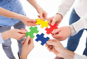 Personal Work Styles photo of close-up of five people hand holding colorful puzzle