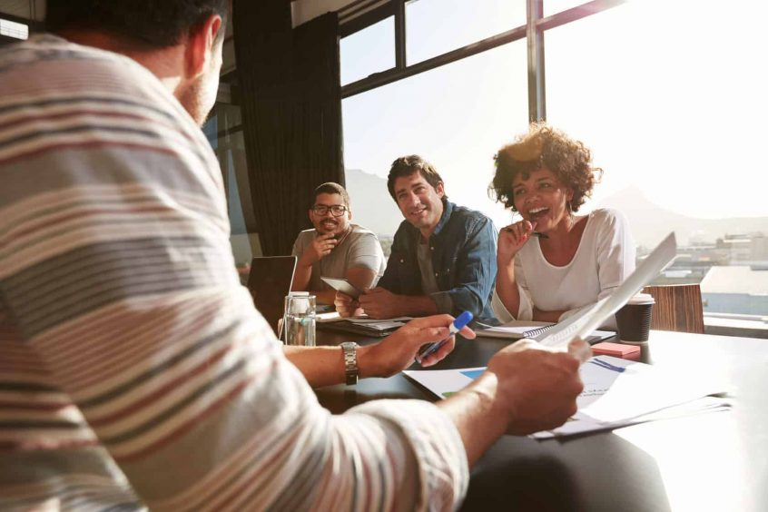 52328670 - shot of young people sitting at a table discussing new and creative business ideas. smiling sitting with colleagues in a meeting.