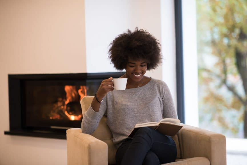 woman drinking cup of coffee reading book at fireplace. young black girl with hot beverage relaxing heating warming up. autumn at home.