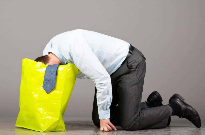 Business man getting sick in bag at holiday office party