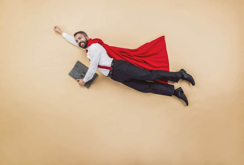 manager in a flying pose wearing a red cloak. on a beige background.