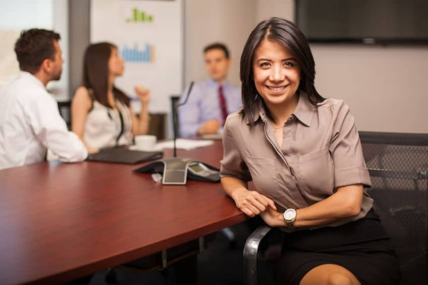 young lawyer sitting in a meeting room with some of her colleagues and smiling