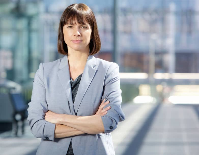 close up portrait of a serious business woman in gray suit standing in the city