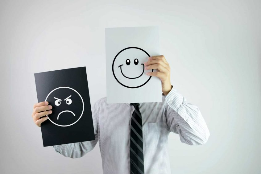 businessman holding two papers with happy and angry face each on them