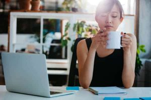 Mindful Leadership Workshop photo of relaxed young woman sitting at her desk and having coffee