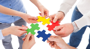 Respectful workshops photo of close-up of five people hand holding colorful puzzle